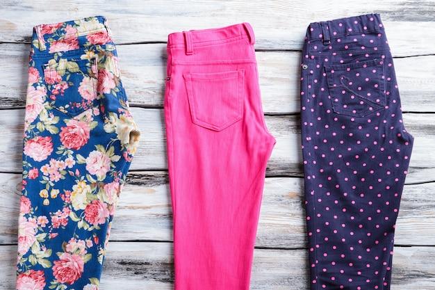 밝은 핑크와 네이비 팬츠. 세련된 프린트의 팬츠. 흰색 선반에 여자 의류입니다. 레귤러 핏 팬츠 판매합니다.