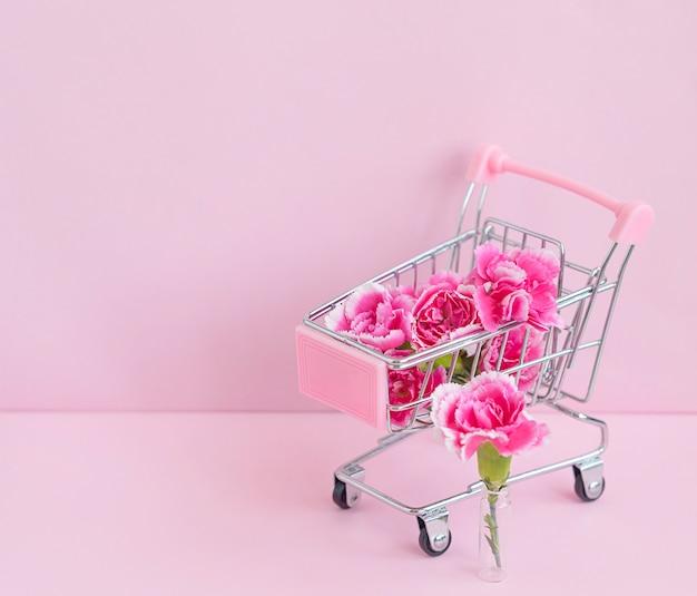 ピンクの背景のカートに明るいピンクのカーネーションの花、家に花や植物を届けるというコンセプト