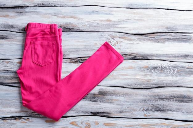 밝은 핑크색 캐주얼 팬츠. 나무 바탕에 분홍색 바지입니다. 소녀의 새로운 바지. 고급 원단과 따뜻한 색감.