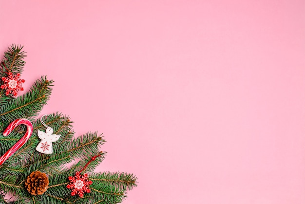 Ярко-розовый новогодний фон с еловыми ветками, украшениями, деревянными игрушками, рождественской конфетной карамелью, сосновыми шишками.
