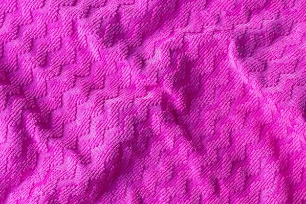 ジグザグパターンの明るいピンクの生地の質感。しわくちゃのラフなテキスタイルの背景