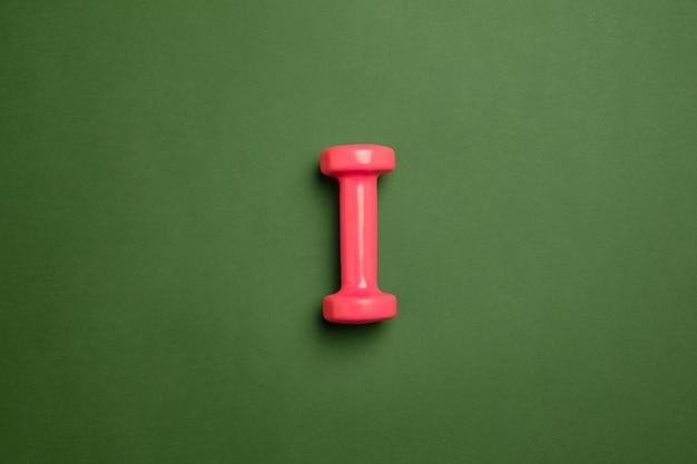 明るいピンクのフィットネス、ボディービルの重み。緑の背景に分離されたプロスポーツ用品。