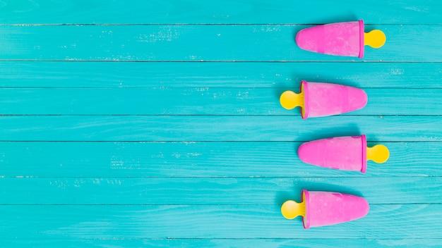 Ghiaccioli congelati rosa luminoso su bastoni gialli su fondo di legno