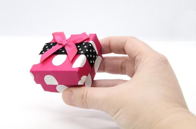 Ярко-розовая подарочная коробка в белый горошек с алой лентой в руке на белом фоне