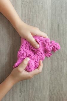 子供の手に明るいピンクのキネティックサンド