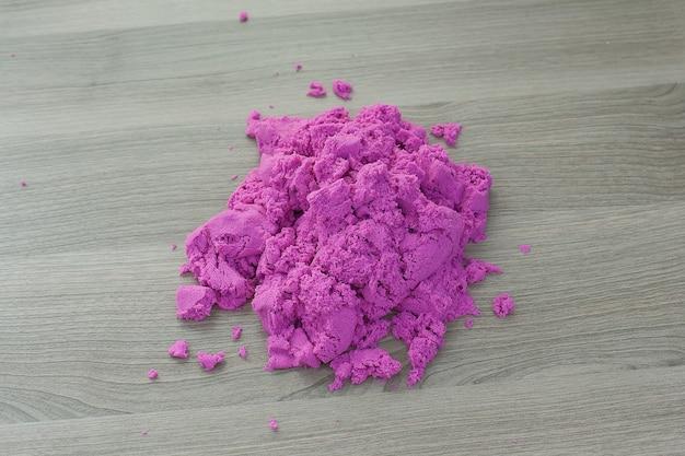 아이의 손에 밝은 분홍색 운동 모래