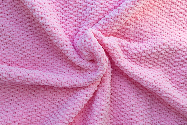 Bright pink knitted plaid made of soft plush yarn