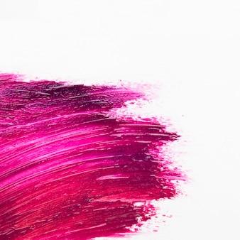 Bright pink nail polish brush stoke over white surface