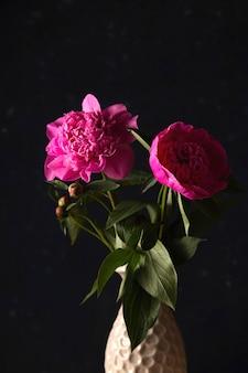 Bright pink peonies in a dark minimal style.