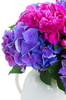 明るいピンクの牡丹と青いオルテンシア生花の花束は、白で隔離のクローズアップ