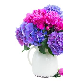 鮮やかなピンクの牡丹、トルコギキョウ、花瓶の青いオルテンシア生花の花束は、白で隔離のクローズアップ