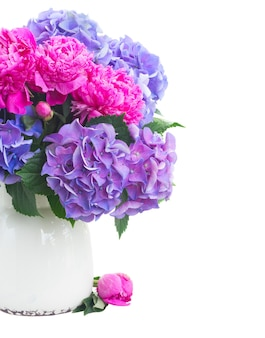 明るいピンクの牡丹、トルコギキョウと青いオルテンシア花瓶の新鮮な花の束は、白で隔離のクローズアップ