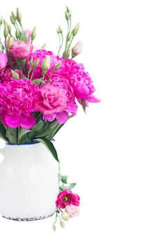 Bright pink peony and eustoma flowers bouquet in pot close up isolated on white Premium Photo