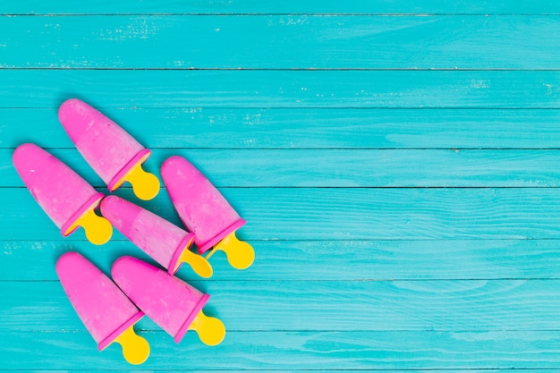 Bright pink popsicles on yellow sticks on wooden turquoise background