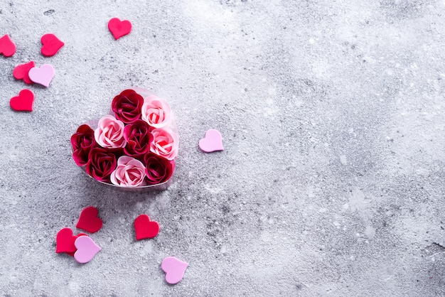 Bright pink and red roses made of soap shavings with hearts on stone, in a heart-shaped box.