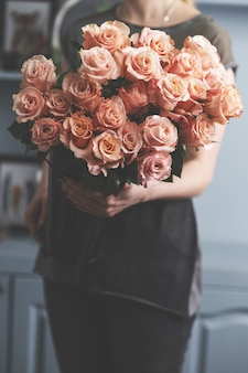 女性の手に明るいピンクのスプレーバラ。