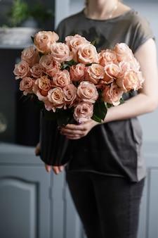 女性の手で明るいピンクスプレーバラ