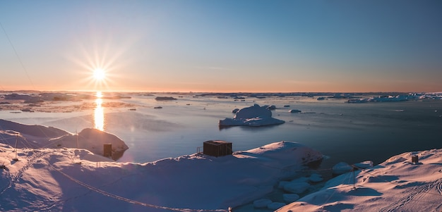 Bright pink sunset over the antarctica shoreline and vernadsky station. amazing panoramic view of the sunlit polar bay. the snow covered surface of the south pole next to the frozen water surface.