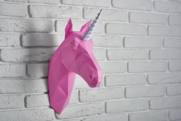 Голова ярко-розового единорога, сделанная из бумаги, висящей на белой кирпичной стене.