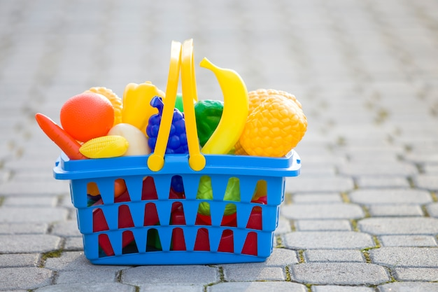 Bright plastic colorful basket with toy fruits and vegetables