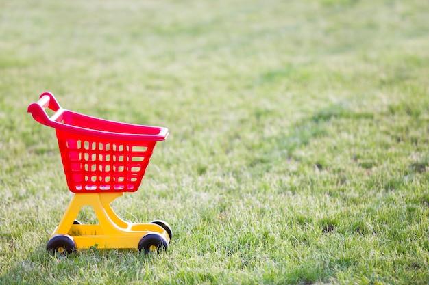 日当たりの良い夏の日に屋外の明るいプラスチック製のカラフルなショッピングカートのおもちゃ。