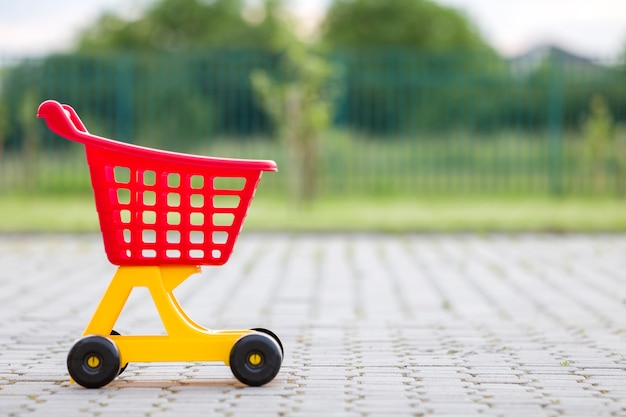Bright plastic colorful shopping cart toy outdoors on sunny summer day.