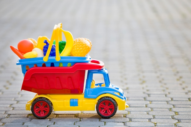 Bright plastic colorful toy car truck carrying basket with toy fruits and vegetables outdoors on sunny summer day