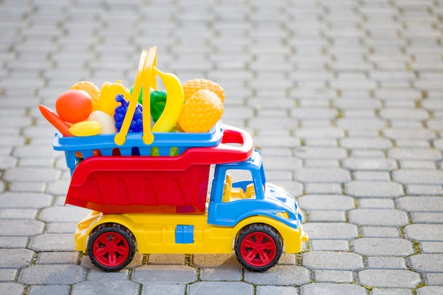 Bright plastic colorful toy car truck carrying basket with toy fruits and vegetables outdoors on sunny summer day.