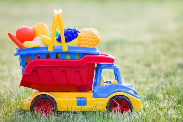 Bright plastic colorful toy car truck carrying basket with toy fruits and vegetables outdoors