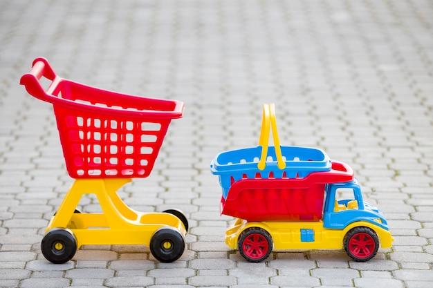 晴れた夏の日に屋外の子供たちのための明るいプラスチックのカラフルなおもちゃ。車のトラック、バスケット、ショッピングの手押し車。