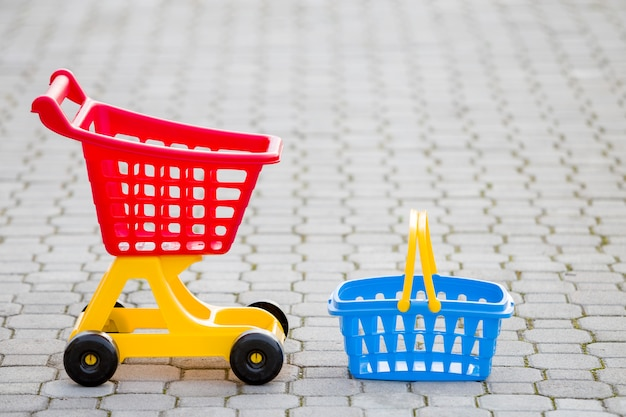 Bright plastic colorful toys, shopping cart and basket outdoors on sunny summer day.