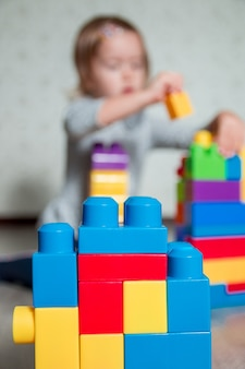 背景に認識できない子供の女の子と明るいプラスチック製の建設ブロック。おもちゃの開発。初期の学習。