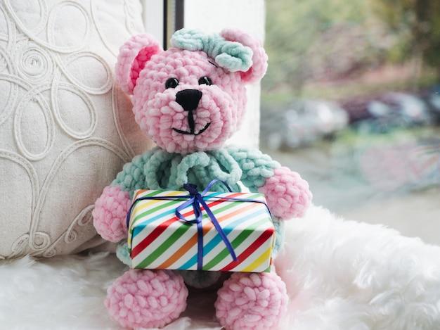Bright plush toy sitting on a windowsill