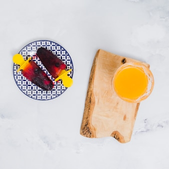 Bright popsicles on plate and glass with juice on wooden stand on gray surface