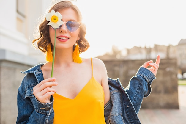 Ritratto luminoso di bella donna che tiene fiore, vestito giallo, giacca di jeans, stile hipster, tendenza moda estiva, sorriso, occhiali da sole alla moda