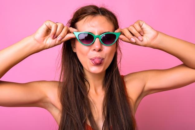 Brillante ritratto di bruna giovane donna che indossa occhiali da sole alla moda occhi di gatto verde