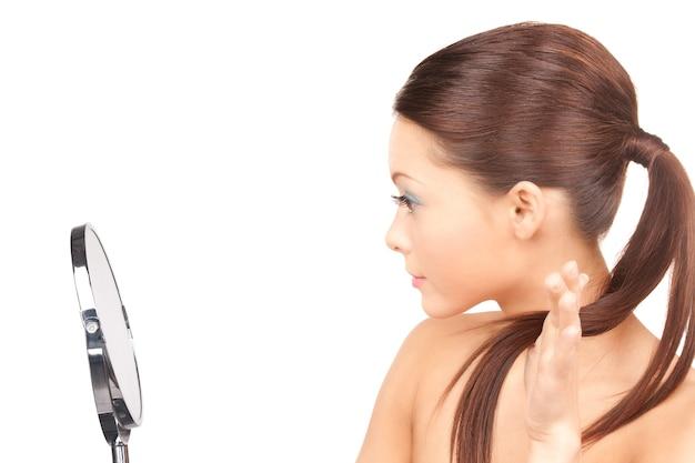 거울을 가진 아름 다운 여자의 밝은 초상화