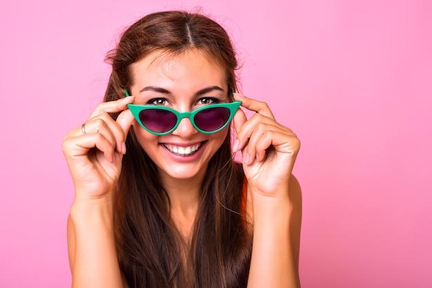トレンディな猫の目の緑のサングラスを身に着けているブルネットの若い女性の明るい肖像画