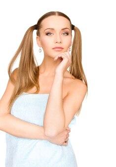 흰 벽에 수건에 사랑스러운 여자의 밝은 초상화