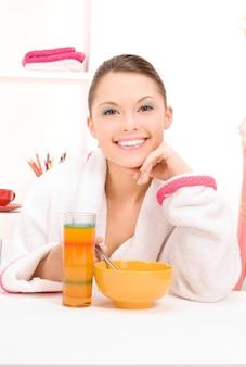 그녀의 아침 식사를 먹는 여자의 밝은 초상화