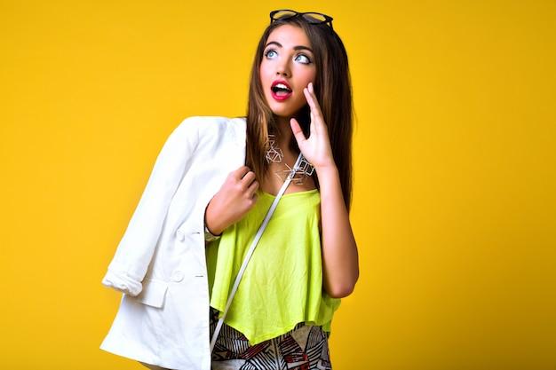 Яркий позитивный модный портрет красивой молодой женщины, стильный модный неоновый наряд, элегантный кэжуал, милые эмоции, цветной поп