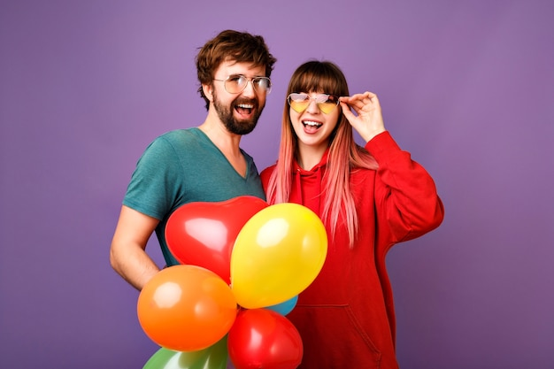 Bright positive  lifestyle portrait of couple hipsters having fun, showing tongues and holding party air balloons, best friends together, casual sportive clothes