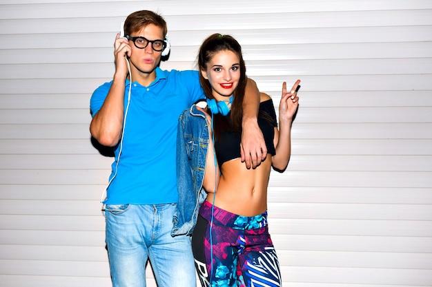 Brillante ritratto positivo di coppia hipster piuttosto sexy che impazzisce insieme, vestiti e accessori luminosi, emozioni giocose positive, gioia, festa. look sportivo urbano street style