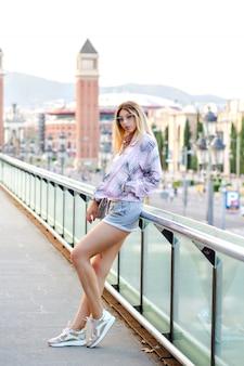 バルセロナ広場でポーズをとって、流行に敏感なトレンディなスポーティな服を着て、フィットして実行している、一人で旅行する、柔らかな色調の幸せなブロンドの女性の明るい肯定的な日当たりの良い春の肖像画。