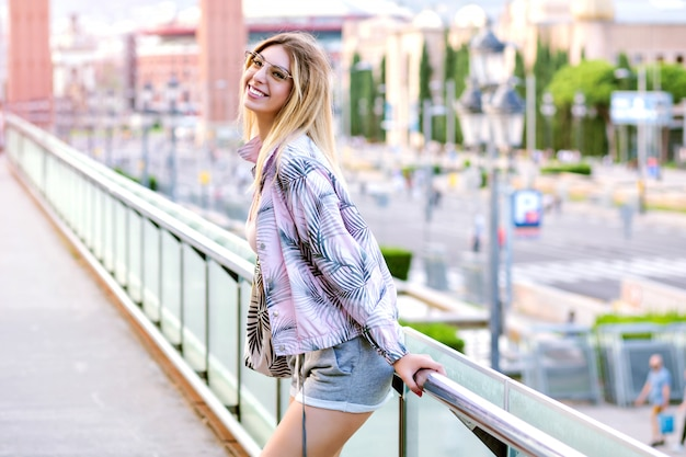 バルセロナ広場でポーズをとって、流行に敏感なトレンディなスポーツ服を着て幸せな金髪女の明るい肯定的な日当たりの良い春の肖像画