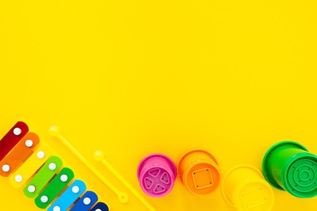 노란색 배경에 밝은 무지개 어린이 실로폰 및 피라미드. 어린이 장난감, 평면도, 평면 배치, 복사 공간 구성.