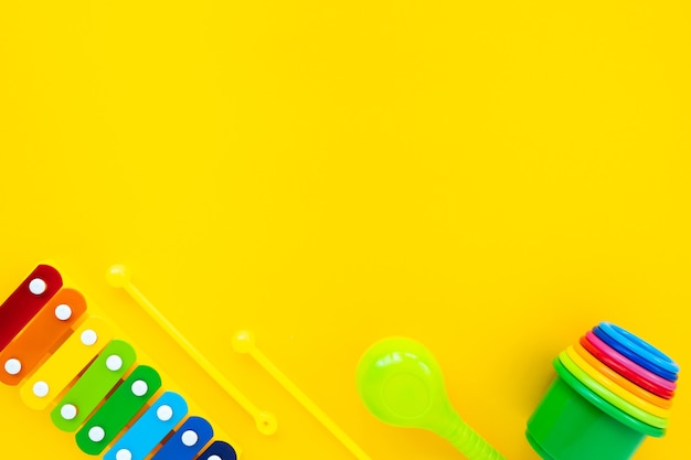 Bright rainbow children's xylophone and pyramid on a yellow background