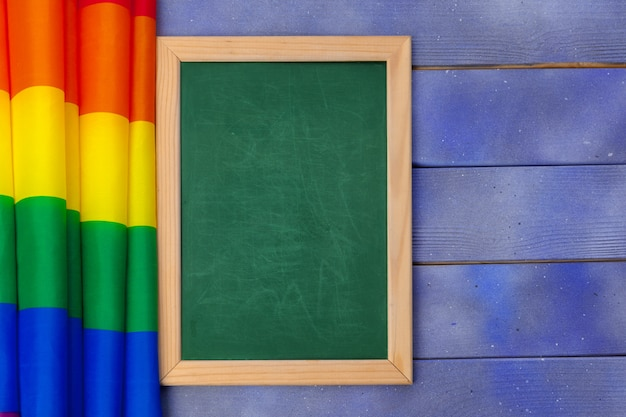 Bright rainbow gay flag on wooden background and blank greenboard