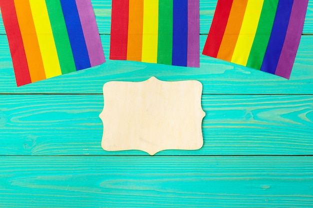 Bright rainbow gay flag on wooden background and blank space