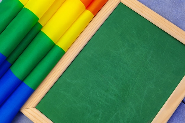 Bright rainbow gay flag on wooden  and blank space